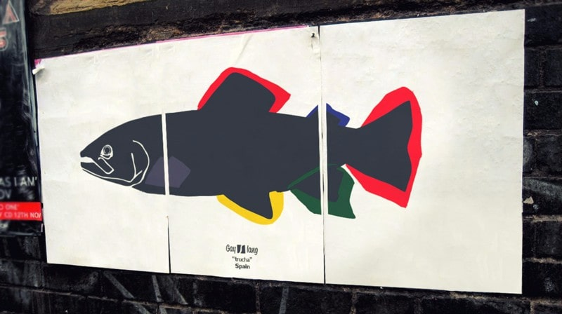 Photograph of a poster in three pieces stuck on a street with the Trucha drawing.