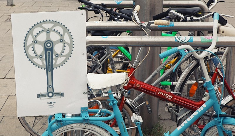 Photograph of a few parked bicycles, in the first of them there is a poster with the illustration Pédale.