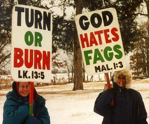 Dos mujeres de la secta con pancartas donde se lee God Hates Fags