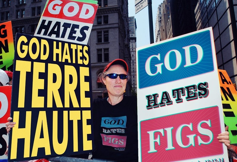 Photograph of the owner of the Baptist Sect of Westboro with a sign saying that God hates figs.