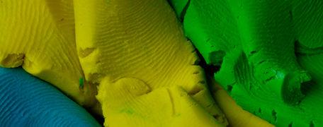 Plastilina en primer plano de colores azul, amarillo y verde con marcas de huellas.