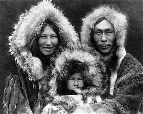 Black and white photo of an Inuit family, wearing fur coats.
