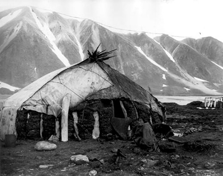 Inuit house is a hut made of stone, peat and leather. In the background great mountains. Black and white photo.