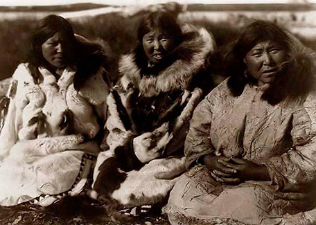 Three Inuit women in the past. White and brown photo.