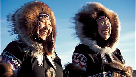 Two smiling Inuit women, dressed in their typical coats, under blue sky.