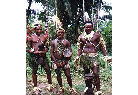 Picture of three members of the Sambia tribe in the jungle, carrying drums.