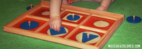 Baby playing to fit pieces on a board without following the shapes (rules).