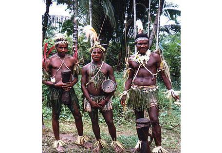 Fotografía de tres miembros de la tribu Sambia en la selva, portando tambores.