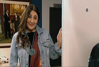 "A frame of the Spanish tv-series ""La que se avecina"". Araceli Madariaga, could be an Earthy-crunchy dyke., in the vain of a door with his face of infinite comprehension."