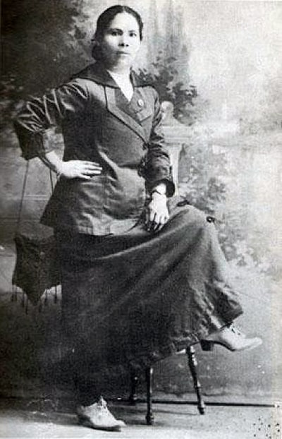Juana Gallo, photographed in black and white, with one leg on a stool.