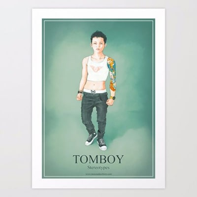 Photograph of a framed poster with the Tomboy design, a masculine girl drawn on a green background. In the lower part, the word Tomboy is read in large.