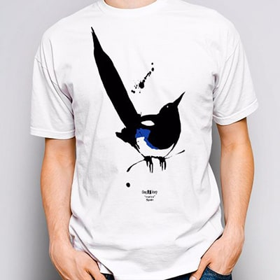 Close-up photograph of a white T-shirt worn by a boy with the Marica design, a magpie in black, white and blue colors
