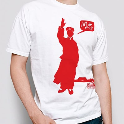 Close-up photograph of a white T-shirt worn by a boy with the Tóngzhì (同志) drawing in red.