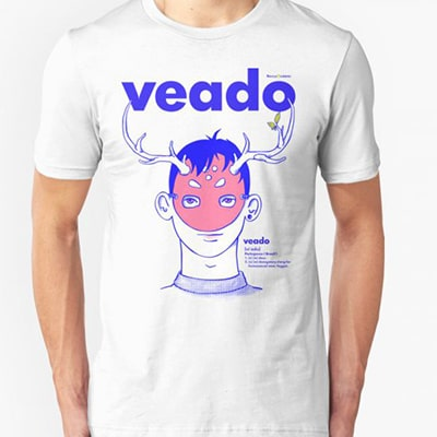 Close-up photograph of a white T-shirt worn by a boy with the Veado drawing, the bust of a boy with a mask with deer horns, with the word veado on the top, in blue and pink colors.