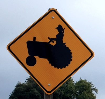 Road sign with a woman on a tractor, which could be considered a virago.