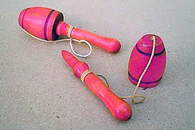 Photograph of a traditional toy called ball-and-stick or cup-and-ball and refers to a traditional toy consisting of a ball with a hole tied to a stick, whose name in French is Bilboquet