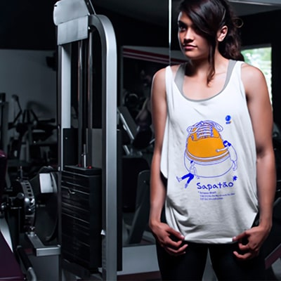 Photograph of a girl in a gym showing a shirt with the Sapatão drawing.