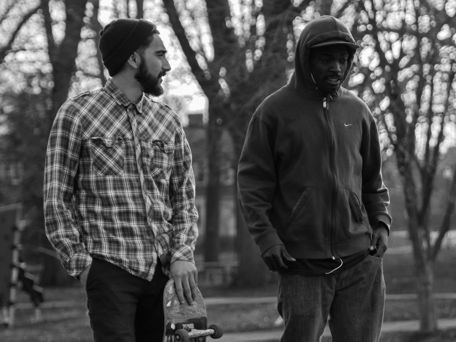 g0y bromance, black and white photo of two friends talking while walking in the park, one of them is a skateboarder.