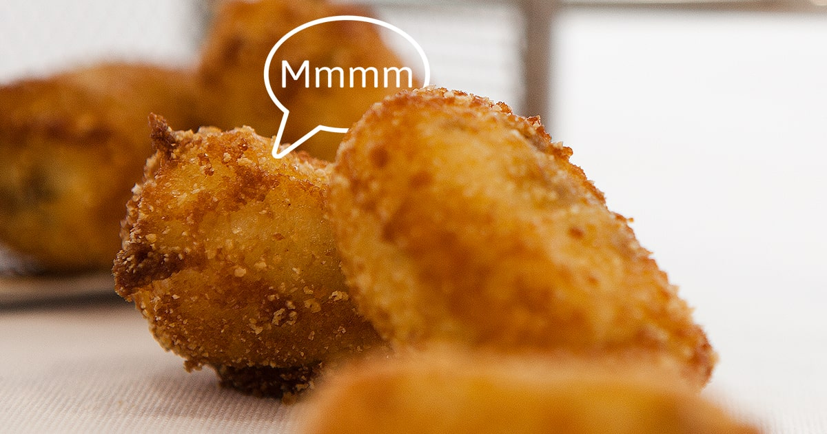 one croqueta (croquette) on top of another with a speech bubble that says ummm