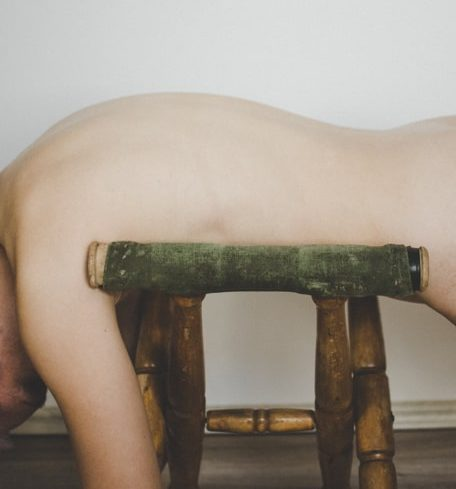 naked woman on stool, image focused on the curve of the back