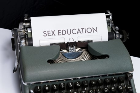 A typewriter in which the text Sex Education appears, whish is necessary to understand Sexual Identity